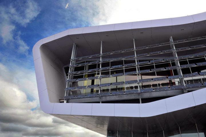 Architecture, conçu par l'architecte Jacques Ferrier, nef de métal et ossature transparente semblant en suspension au-dessus des quais et rejoignant « la Tour des vents ».